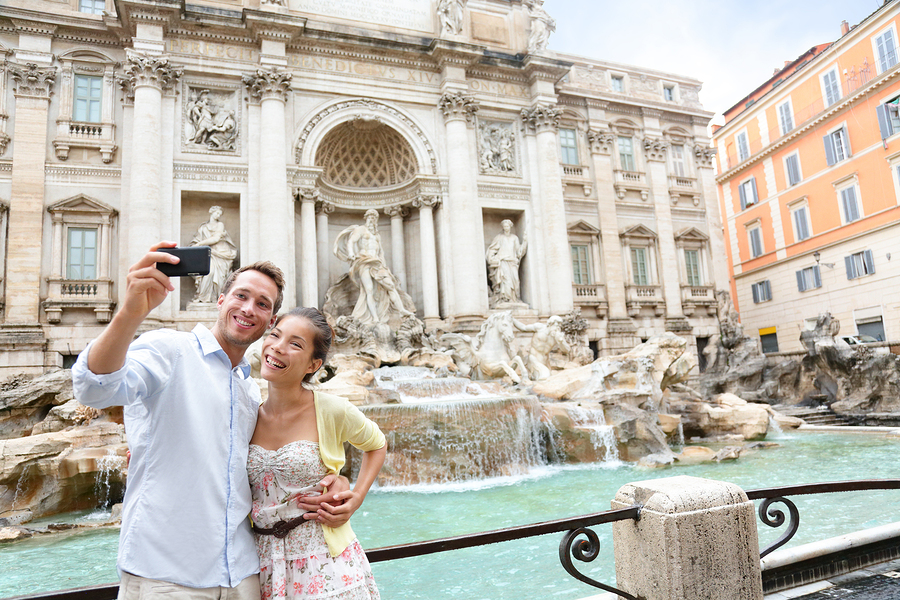 Tourist couple on travel taking selfie photo by Trevi Fountain i